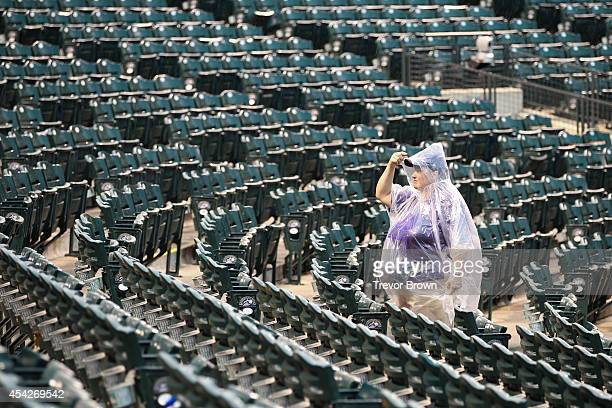 An usher in a rain poncho waits out the rain delay before the start of the game between the Colorado Rockies and the Chicago Cubs at Coors Field on...