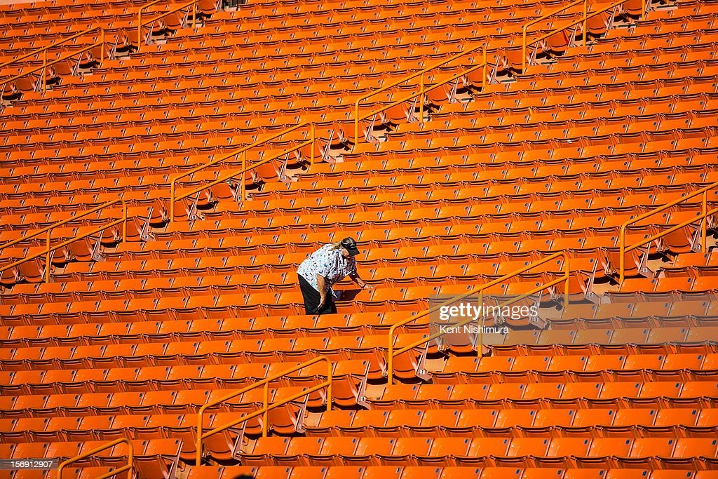 An usher is seen cleaning the stands before the start of a NCAA college football game between the UNLV Rebels and the Hawaii Warriors on November 24, 2012 at Aloha Stadium in Honolulu, Hawaii.