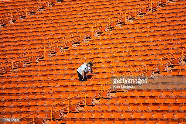 An usher is seen cleaning the stands before the start of a NCAA college football game between the UNLV Rebels and the Hawaii Warriors on November 24...