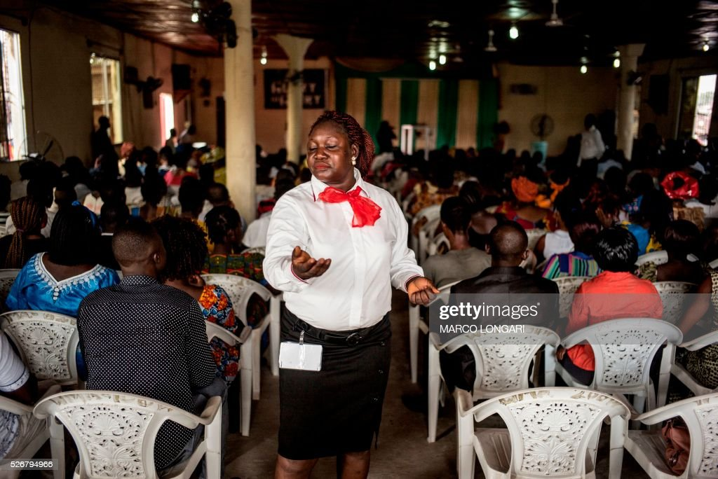 An usher prays during a service at the Winners Chapel International in the Weasay district of Monrovia on May 1, 2016. / AFP / MARCO