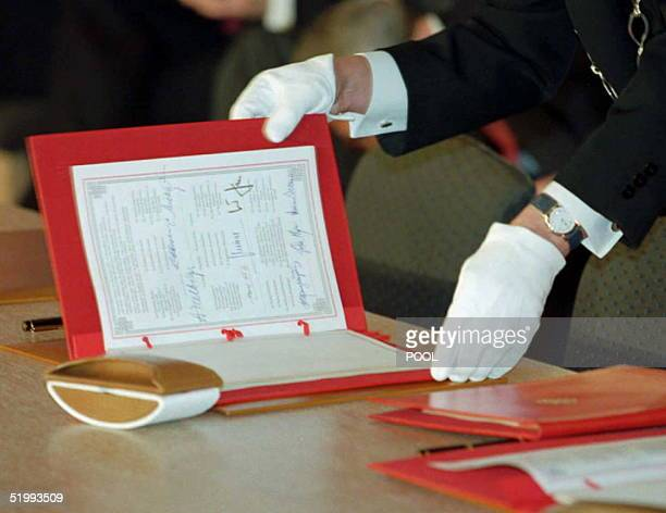 An usher shows the treaty for peace in Bosnia which was signed by Balkan US Russian and European leaders 14 December in order to forge an end to...