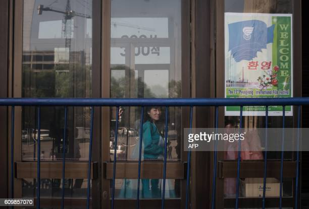 TOPSHOT An usher waits to check tickets at an entrance to the Pyongyang International Cinema during the 15th Pyongyang Film Festival in the capital...