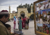 An Uyghur man and his son look at photos as women stand in front of the Id Kah Mosque China's largest mosque on July 31 2014 in Kashgar Xinjiang...