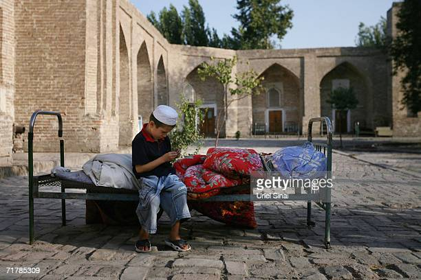 An Uzbek boy sits in the courtyard of the local mosque and madrasa where he lives and studies Islam on August 12 2006 in Kukand near Margilan in the...