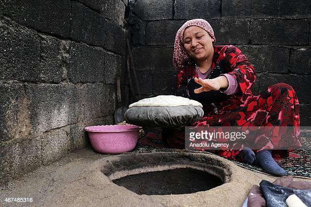 An Uzbek woman prepares bread prepares at tandouri in Ovakent neighbourhood of Hatay province in south eastern Turkey on February 14 2015 Uzbek...