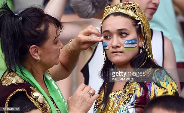 An Uzbekistan fan paints a flag on a woman's face before the start of the Asian Cup quarterfinal football match between South Korea and Uzbekistan in...