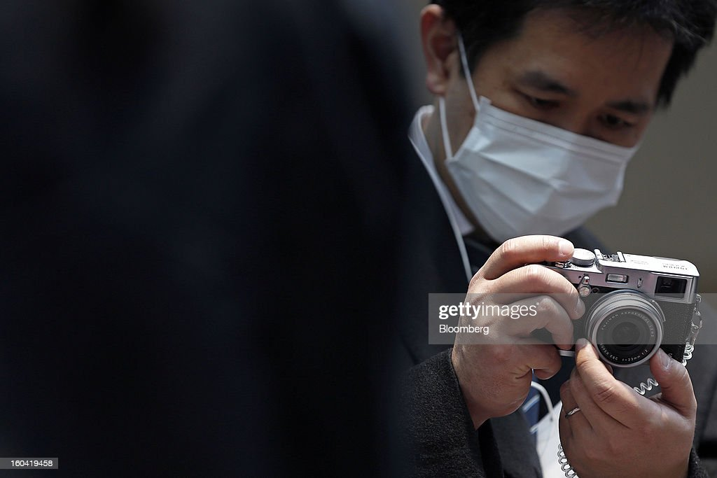 An visitor wears a mask as he looks at a Fujifilm Holdings Corp. X100S digital camera at the CP+ Camera and Photo Imaging Show in Yokohama City, Japan, on Thursday, Jan. 31, 2013. The CP+ Camera and Photo Imaging Show runs from Jan. 31 to Feb. 3. Photographer: Kiyoshi Ota/Bloomberg via Getty Images