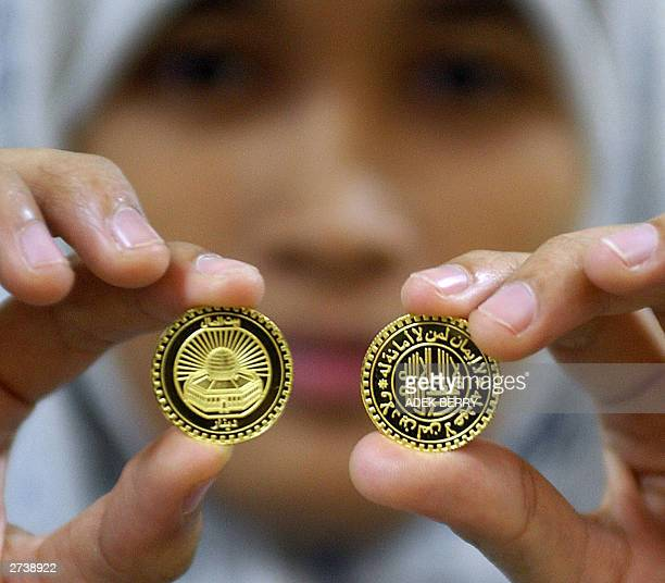 An woman shows a gold token from a Indonesian Muslim business group Baitulmaal Muamalat featuring the alAqsha mosque and with writings 'there is no...