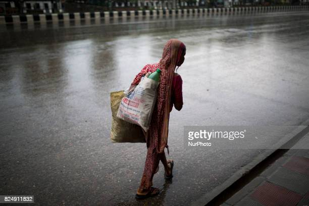 An women seen on street searching waste plastic bottle during rain in Dhaka Bangladesh on July 31 2017