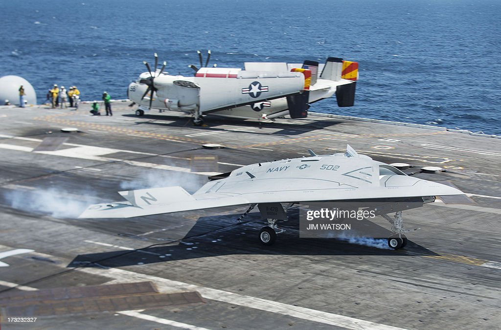 An X-47B Unmanned Combat Air System (UCAS) makes the very first carrier landing aboard the USS George H.W. Bush while afloat in the Atlantic Ocean off the coast from Norfolk, Virginia, on July 10, 2013. AFP PHOTO/JIM WATSON