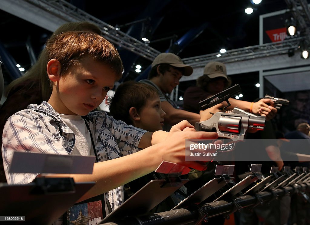 An young attendee inspects a handgun during the 2013 NRA Annual Meeting and Exhibits at the George R. Brown Convention Center on May 4, 2013 in Houston, Texas. More than 70,000 peope are expected to attend the NRA's 3-day annual meeting that features nearly 550 exhibitors, gun trade show and a political rally. The Show runs from May 3-5.