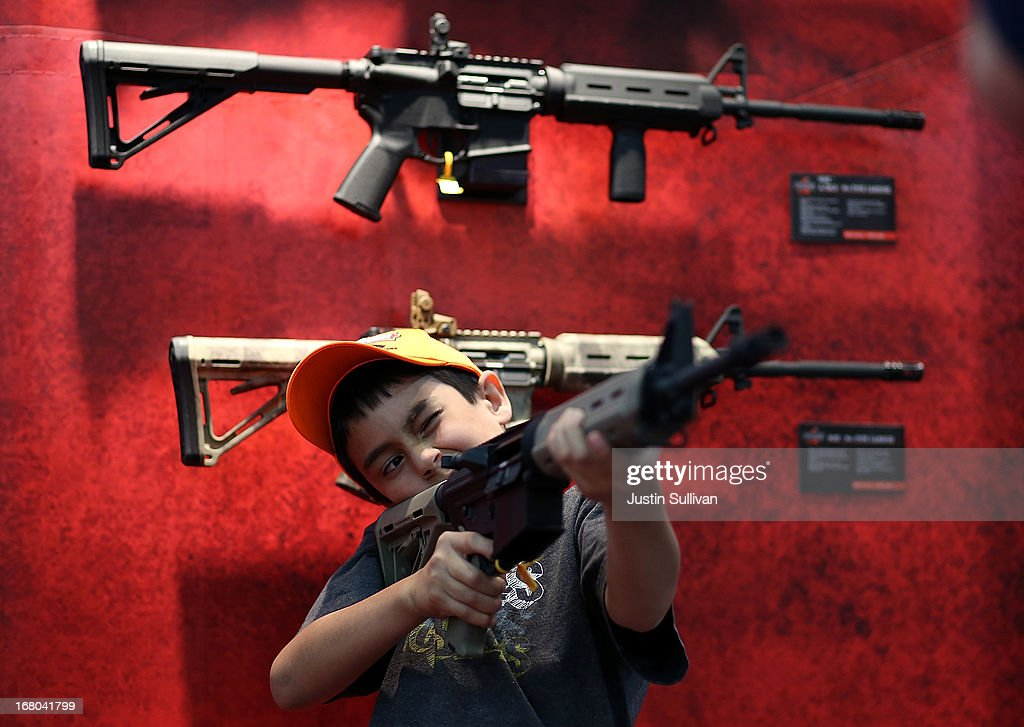 An young attendee inspects an assault rifle during the 2013 NRA Annual Meeting and Exhibits at the George R Brown Convention Center on May 4 2013 in...