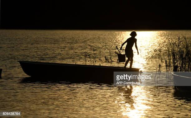 An young boy leaves a boat at the shore of the small lake in the Spreewald area near Cottbus eastern Germany during sunset after a hot summer day...