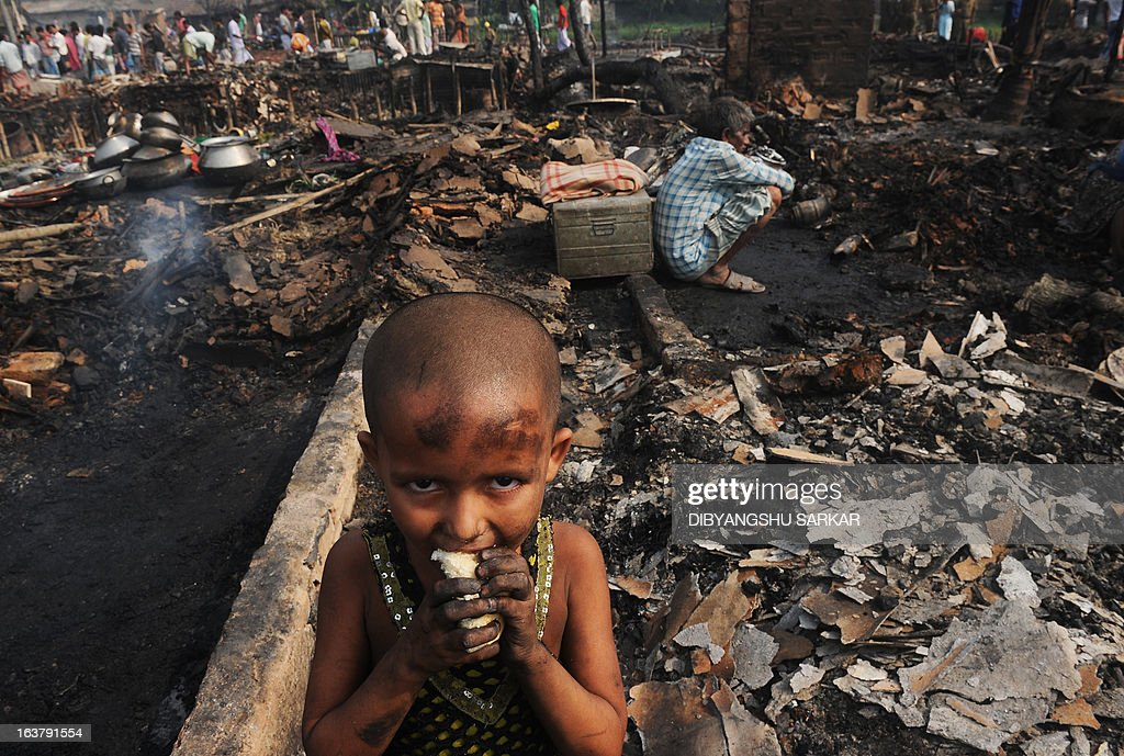 An young Indian slum dweller eats bread standing near gutted shanties in the Santoshpur area on the outskirts of Kolkata on March 16, 2013. Around 700 shanties were gutted in a fire leaving more than a thousand people homeless. Police said no injuries or casualties were reported. AFP PHOTO/ Dibyangshu SARKAR