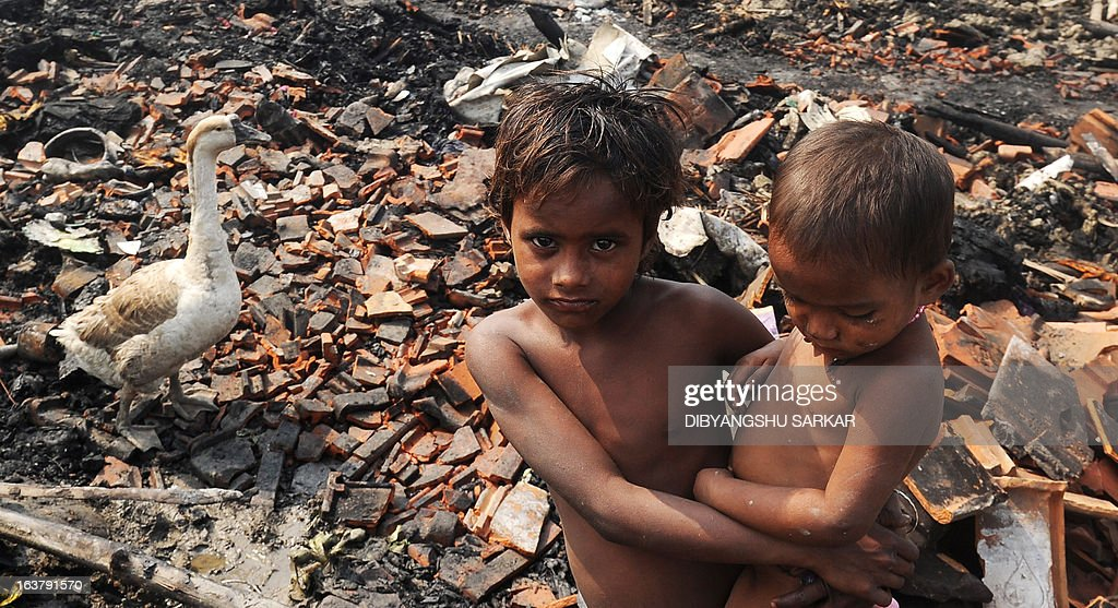 An young Indian slum dweller looks on standing near gutted shanties in the Santoshpur area on the outskirts of Kolkata on March 16, 2013. Around 700 shanties were gutted in a fire leaving more than a thousand people homeless.Police said no injuries or casualties were reported. AFP PHOTO/ Dibyangshu SARKAR
