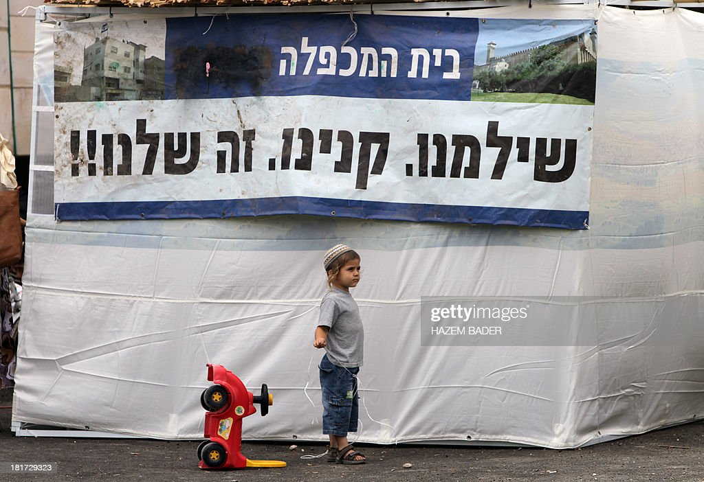 An young Israeli settler stands next to poster hanging on a protest tent reading in Hebrew: 'We paid and bought so it's ours' erected in front of the house of the Palestinian Abu Rajab family, as they demonstrate on September 24, 2013 against the eviction of settlers from the building last year in the West Bank city of Hebron. Israeli Prime Minister Benjamin Netanyahu ordered the resettlement of the disputed Machpela house, a Hebron structure near the Cave of the Patriarchs from which he had removed 15 Jewish settlers last year, following the killing of an Israeli soldier. AFP PHOTO/HAZEM BADER