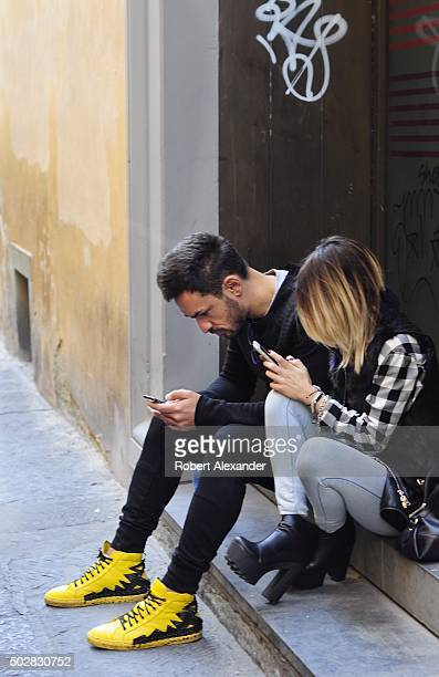 An young Italian couple use their smartphones as they sit beside a sidewalk in Florence Italy