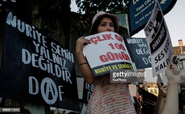 An young woman holds a placard during a protest in support of sacked academic Nuriye Gulmen and primary school teacher Semih Ozakca who were arrested...