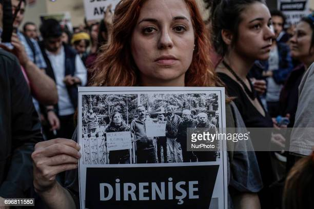 An youth woman holds a placard during a protest in support of sacked academic Nuriye Gulmen and primary school teacher Semih Ozakca who were arrested...