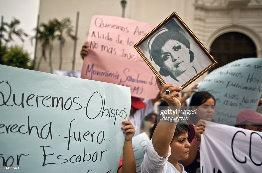 Ana Cisneros (C) raise the portrait of her mother Irma Cisneros, kidnapped by a death squad during the civil war in El Salvador, during a protest against the Catholic Church's decision to close the Legal Tutelage office, in downtown San Salvador, El Salvador on October 6, 2013. The office --shut down last week by San Salvador's bishop Jose Luis Escobar on grounds of 'countable, administrative and legal irregularities'-- investigated mayor crimes during El Salvador's civil war (1980-1992) and keeps historical archives about humans rights violations committed by the military. AFP PHOTO / Jose CABEZAS
