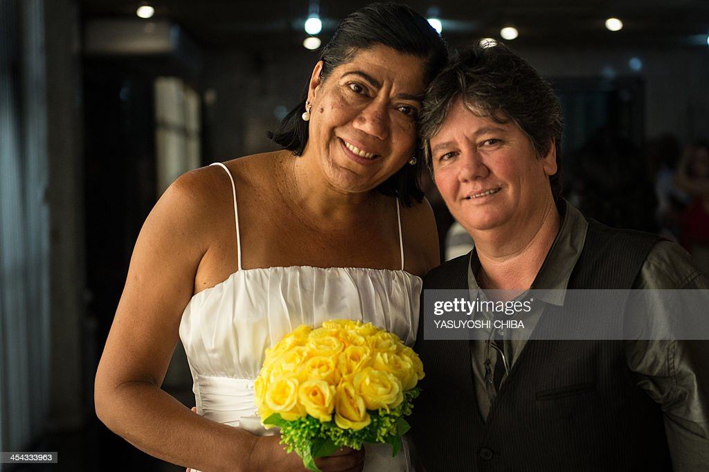 Ana Cristina Ribero Martins (R) and Claudia Almeida Martins pose after the wedding ceremony at the Court of Justice of the State of Rio de Janeiro in Rio de Janeiro, Brazil, on December 8, 2013. 130 gay couples are getting married in the first massive wedding ceremony since the first gay marriage in Rio de Janeiro in 2011.