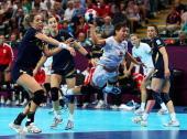 Ana Dokic of Montenegro shoots past Begona Fernandez Molinos and Andrea Barno San Martin of Spain during the Women's Handball semifinal game between...