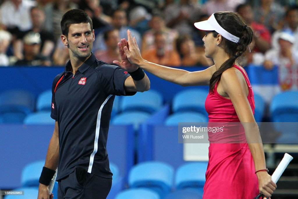 Ana Ivanovic and Novak Djokovic of Serbia high five in their mixed doubles match against Tatjana Malek and Thanasi Kokkinakis of Germany during day seven of the Hopman Cup at Perth Arena on January 4, 2013 in Perth, Australia.
