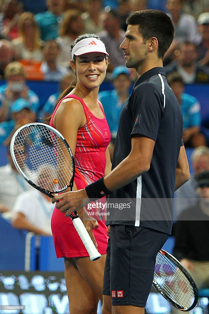 Ana Ivanovic and Novak Djokovic of Serbia talk tactics in their mixed doubles match against Tatjana Malek and Thanasi Kokkinakis of Germany during day seven of the Hopman Cup at Perth Arena on January 4, 2013 in Perth, Australia.