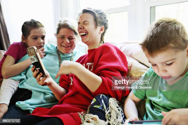 Ana Johnson center laughs during a FaceTime call to her older sister and nephew living in the Ukraine on April 8 2017 Johnson is surrounded by her...