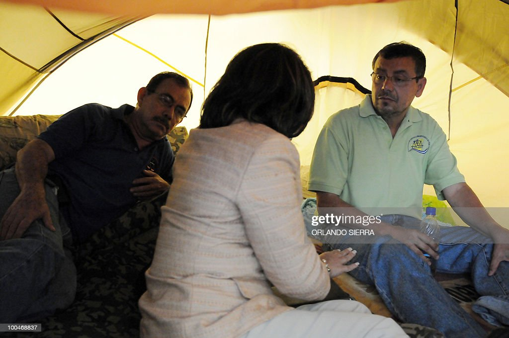 Ana Pineda (C), President Porfirio Lobo's advisor on Human Rights, talks with judges Luis Alonso Chevez (L) and Adan Guillermo Lopez, on hunger strike since seven days ago, at La Merced square in Tegucigalpa, May 24, 2010. Both judges were dismissed by the Supreme Court of Justice for having condemned the June 28, 2009's coup against President Manuel Zelaya. AFP PHOTO/Orlando SIERRA.
