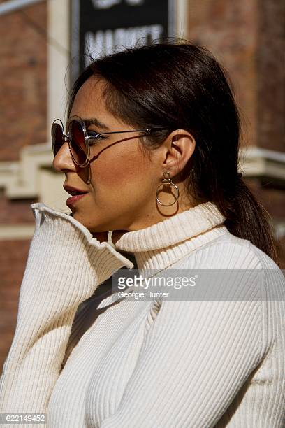 Ana Sousa wearing Ecru white ribbed knit sweater with polo neck and long sleeves with slit from Zara Ralph Lauren gold round orbital drop earrings...