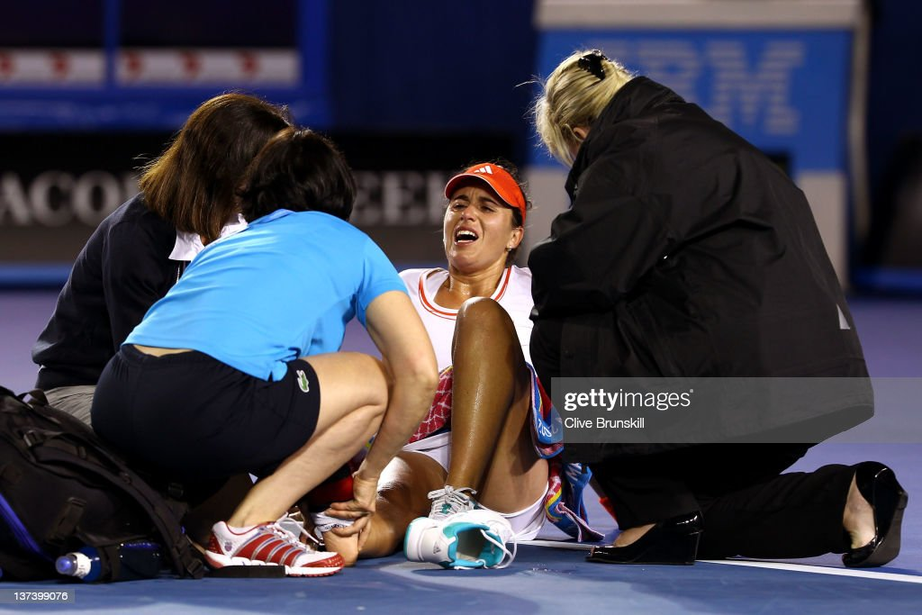 <a gi-track='captionPersonalityLinkClicked' href=/galleries/search?phrase=Anabel+Medina+Garrigues&family=editorial&specificpeople=595904 ng-click='$event.stopPropagation()'>Anabel Medina Garrigues</a> of Spain is attended to by medical staff after injuring her ankle in her third round match against Na Li of China during day five of the 2012 Australian Open at Melbourne Park on January 20, 2012 in Melbourne, Australia.