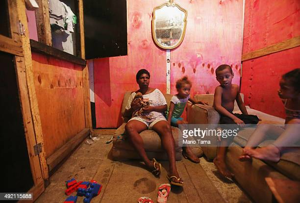 Anacleidi and extended family members sit in her house in an impoverished section of the Mare 'favela' community on October 9 2015 in Rio de Janeiro...
