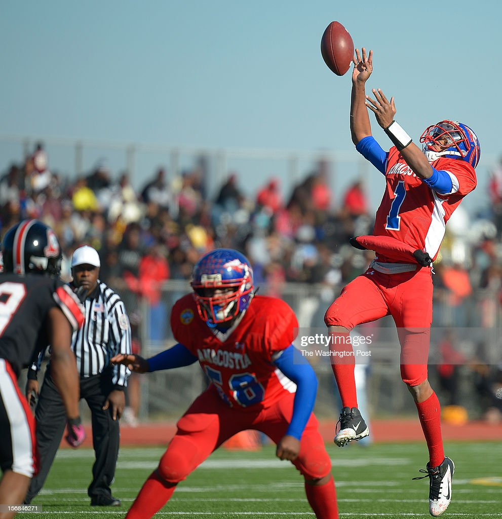 Anacostia's quarterback DeQuan Tuner, right, fumbles a very high 3rd quarter snap in the red zone that was recovered by Dunbar as Dunbar defeats Anacostia 12 - 8 in the Turkey Bowl at Eastern High School in Washington DC, November 22, 2012 .