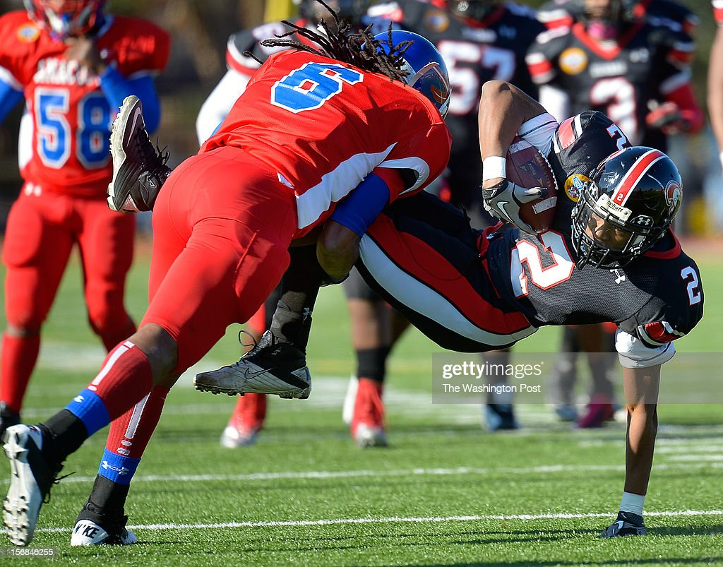 Anacostia's Raequan Reaves, left takes down Dunbar's Delonte Matthews on a reception during Dunbar's defeat of Anacostia 12 - 8 in the Turkey Bowl at Eastern High School in Washington DC, November 22, 2012 .