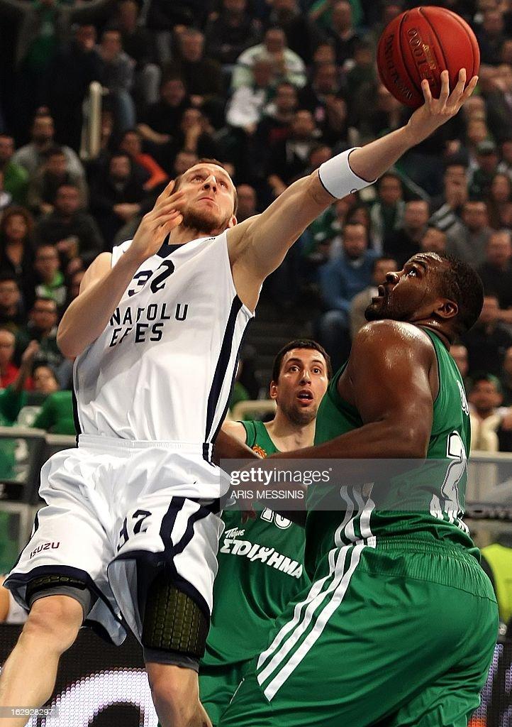 Anadolu Efes' Sinan Guler (L) jumps to score during the Euroleague top 16 basketball game Panathinaikos vs Anadolu Efes in Athens on March 1, 2013.