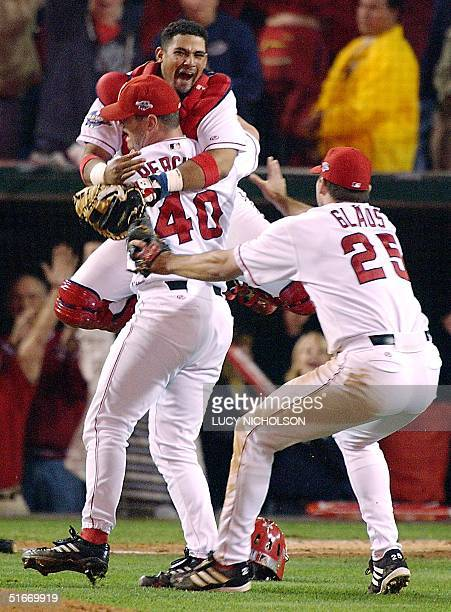 Anaheim Angels catcher Bengie Molina jumps into the arms of closing pitcher Troy Percival as Troy Glaus rushes to celebrate after the last out of...