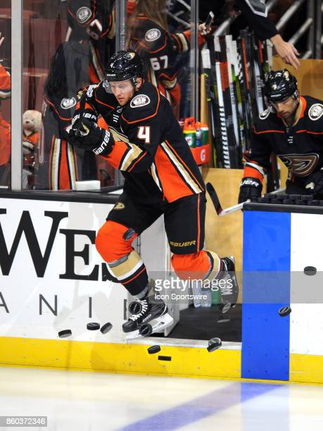 Anaheim Ducks defenseman Cam Fowler knocks a stack of pucks onto the ice during the pre skate before a game against the Calgary Flames on October 9...