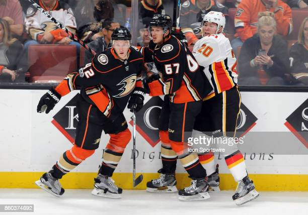 Anaheim Ducks defenseman Josh Manson and center Rickard Rakell in action with Calgary Flames center Curtis Lazar in the second period of a game...