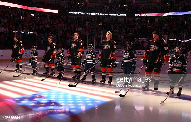 Anaheim Ducks players stand alongside youth hockey players during the national anthem before the game against the Buffalo Sabres on October 22 2014...