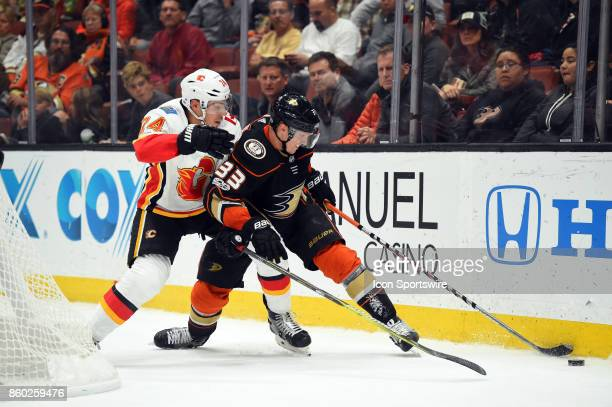 Anaheim Ducks Right Wing Jakob Silfverberg and Calgary Flames Defenseman Travis Hamonic battle for the puck behind the net during an NHL game between...