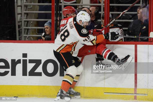 Anaheim Ducks Winger Logan Shaw checks Carolina Hurricanes Winger Janne Kuokkanen into the boards during a game between the Anaheim Ducks and the...