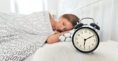 Young woman is sleeping in her bed. Alarm clock in the foreground