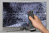 Analog noise on TV and human hand with TV remote controller