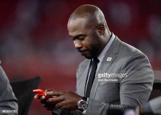TV analyst and Hall of Famer Marshall Faulk checks his phone during an NFL football game between the New England Patriots and the Tampa Bay...