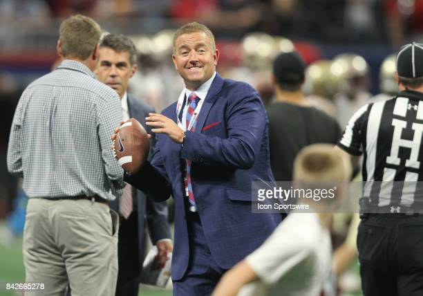 ESPN analyst Kirk Herbstreit throws the football with his son prior to the ChickfilA Kickoff Classic between the Alabama Crimson Tide and the Florida...