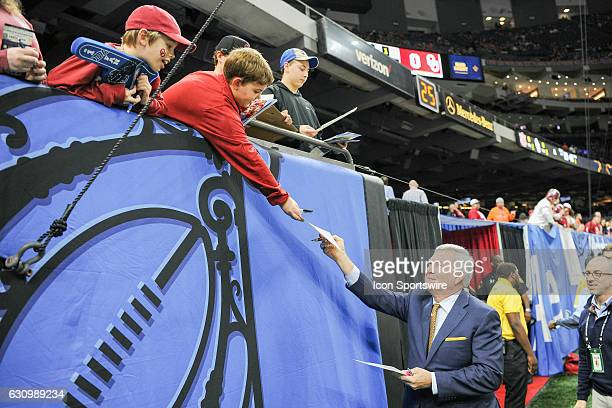 ESPN analyst Mack Brown signs autographs for young fans as he departs the field during the Sugar Bowl game between the Auburn Tigers and Oklahoma...