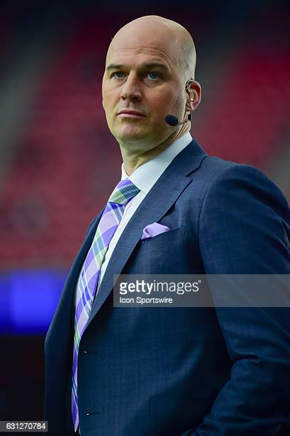 ESPN analyst Matt Hasselbeck watches teams warm up before the NFL AFC Wild Card game between the Oakland Raiders and Houston Texans on January 7 at...
