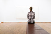 An unrecognizable woman sitting at the art museum and looking at the blank canvas.