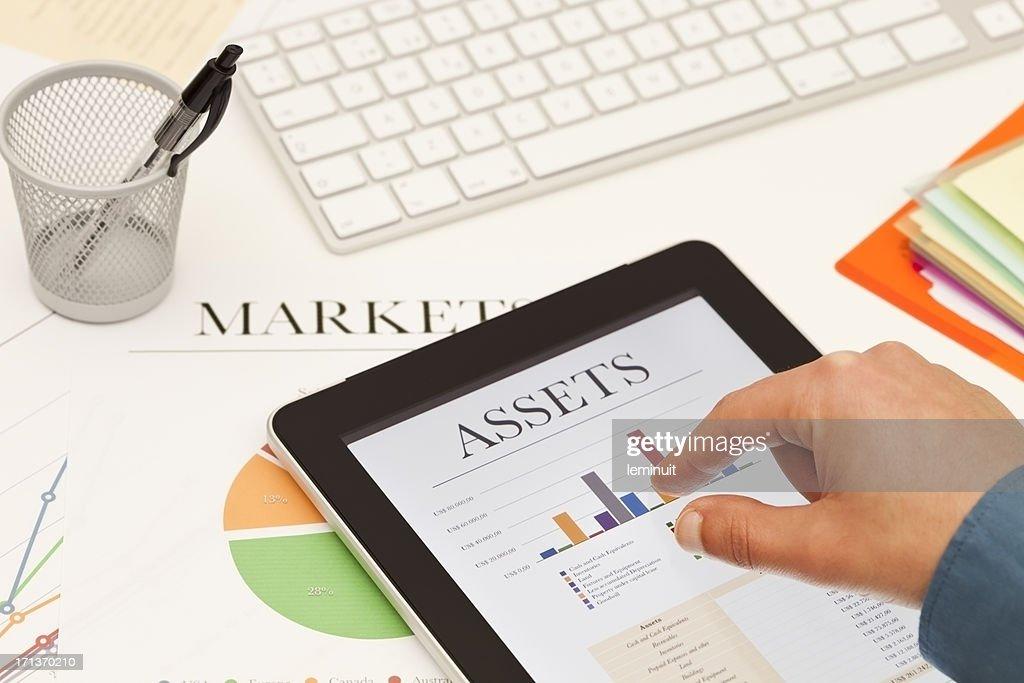Analyzing markets on a digital tablet.